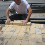 On top of the pavers, lay down a tight-fitting pad of fire bricks. Keep them as even as possible--this will be the floor of the oven.
