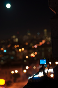 My Canon SD1000 perched on a SF parking garage ledge shooting a full moon timelapse